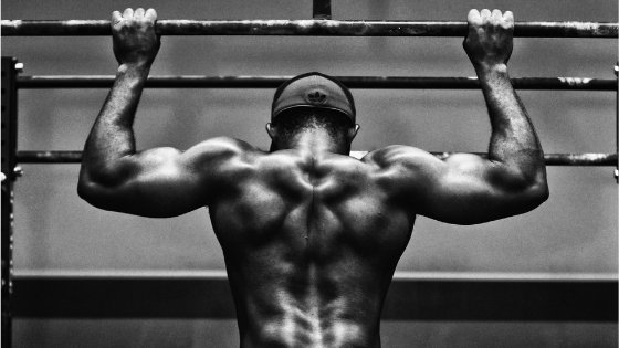 black and white photo of man's back while doing pull-ups